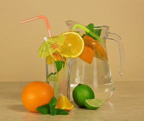 Jug, glass with cocktail, orange and a juicy lime