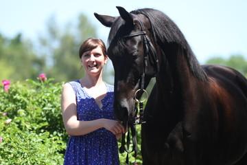Junge Frau mit Pferd vor Blumen