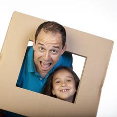 Hombre y niña sacando la cabeza por marco de cartón