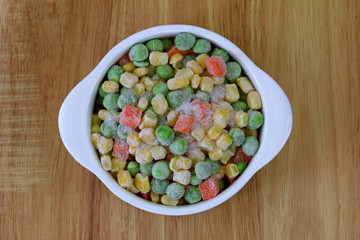A bowl of frozen diced vegetable (corn, peas, carrots)