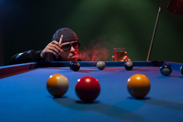 Man playing pool in a club smoking e-cigarette