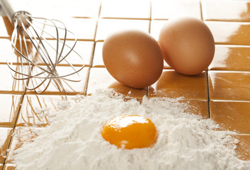 Eggs, flour and whisk on tile