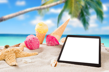 Ice cream with tablet on sandy beach.