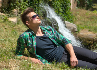 Guy in sunglasses relaxing in nature near the waterfall