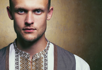 Arty portrait of young and handsome man in white ethnic embroide