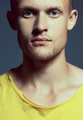 Young handsome and man with pensive look in yellow T-shirt