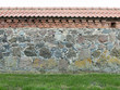 Wall from large granite stones with tile roof and grass as backg