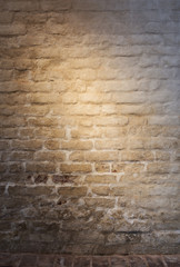 Light patch of light on the old plastered brick wall