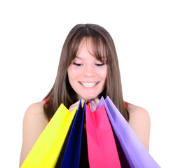 Cute woman looking in colorful shopping bags isolated on white