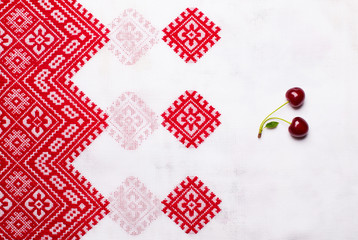 Sweet ripe cherry on bright white Ukrainian tablecloth with red