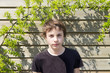 portrait of a teenage boy in front of a wooden wall.