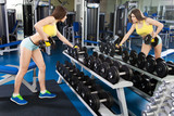 Fototapety Young slim woman exercising in a gym