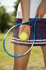 Female hand holding tennis racket