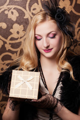beautiful retro woman holding a golden gift box