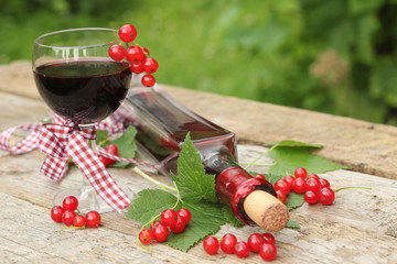 Red currant wine in glass on natural background
