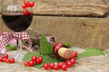 Red currant wine in glass on wooden background