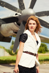 beautiful woman with old suitcase posing against plane