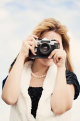 beautiful woman with vintage camera posing outdoors