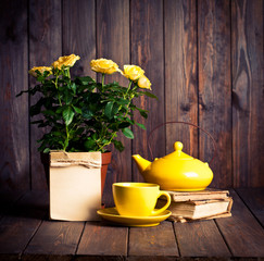 yellow roses in pot, tеapot, tea cup and old books on wooden ta