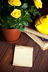 yellow roses in pot, tеapot and old books on wooden table