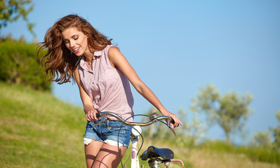 Sexy woman with vinntage bike in a country road.