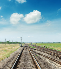 crossing of two railroads and blue sky with clouds