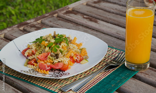 Pasta with vegetables and a glass of fresh orange juice