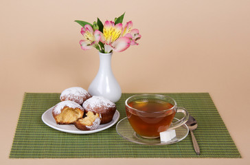 Tea, cupcakes and vase with the flowers