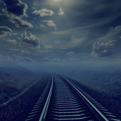 railroad in night to horizon in fog. moonlight in cloudy sky