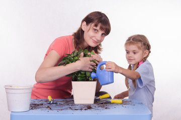 Mom and daughter watering flower pot