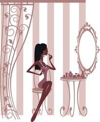 Девушка сидит у зеркала