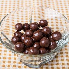 Round chocolate candies in a glass bowl