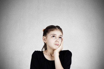 Sad daydreaming teenager girl isolated on grey wall background