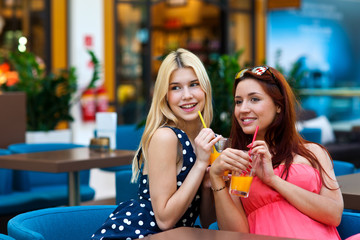 two woman friends drinking juice in bar