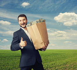 businessman holding paper bag with money