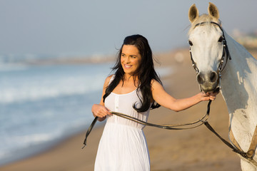 pretty young woman walking a horse on beach