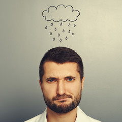 dissatisfied man with drawing storm cloud