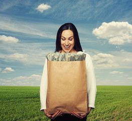 smiley woman holding paper bag with money