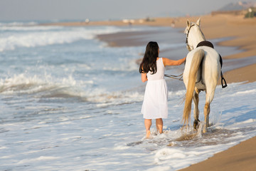 rear view of young woman walking a horse on beach