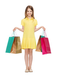 smiling little girl in dress with shopping bags