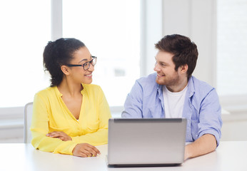 two smiling people with laptop in office