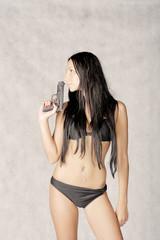 Sexy brunette kissing hand gun toned image