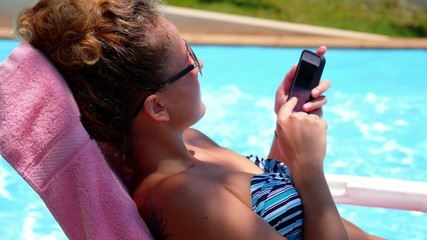 Woman Surfing Internet in the Phone while Relaxing in Pool.