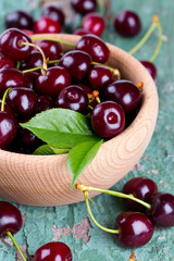 cherries in a bowl on wooden surface