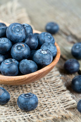 fresh blueberries in a wooden spoon over wooden table