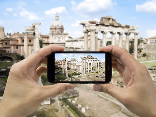 tourist holds up camera mobile at forum in Rome