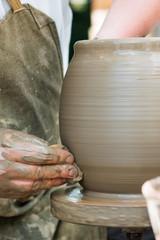 potter's hands working on ceramic jug