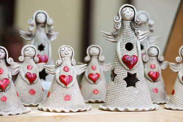 Group of ceramic angels with red heart on wooden table