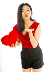 Young woman holding heart shape cushion and blowing kiss