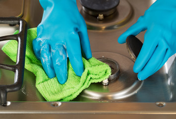 Gloved hands removing soap from stove top range with microfiber